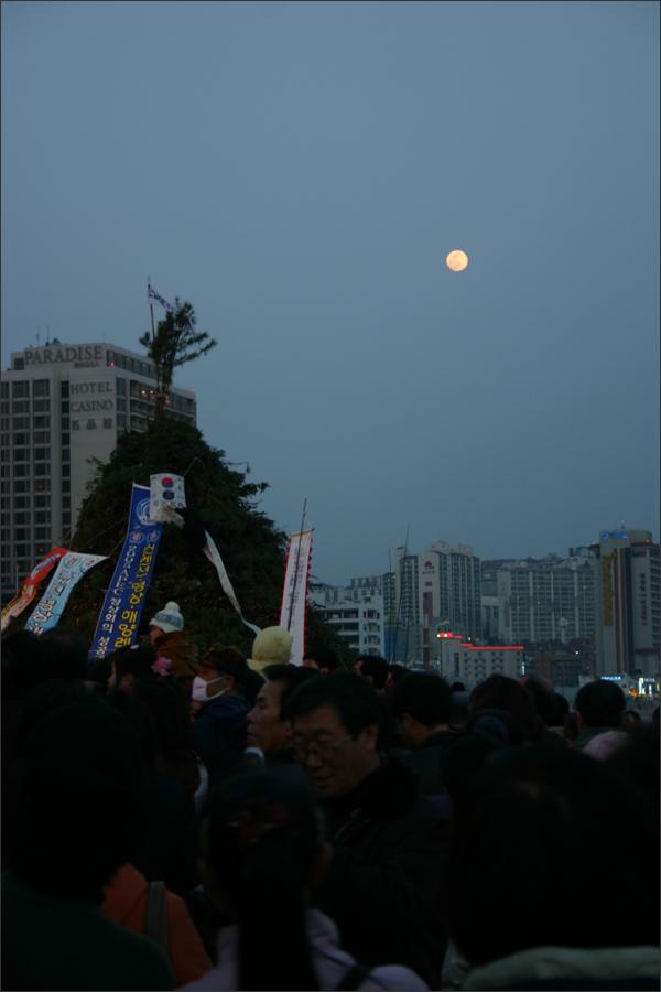내일을 기다리는 사람들 사이로 달이 떠오른다.