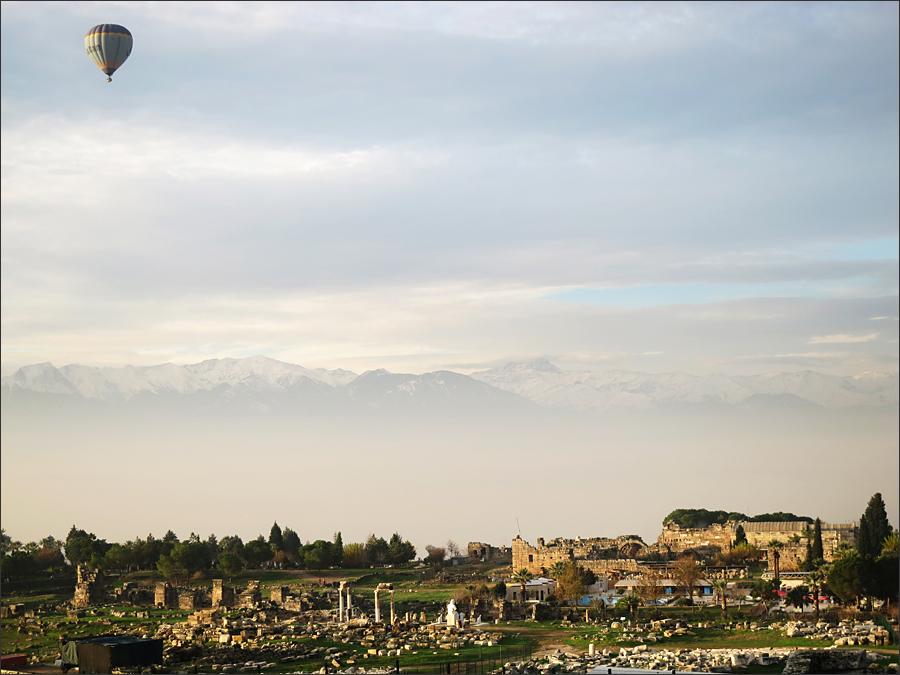 원형극장에서 바라본 히에라폴리스. 흰색의 아폴로 석상 뒤로 타우르스 산맥의 설산이 보인다.